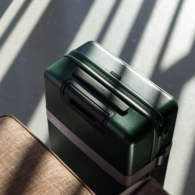 NORTVI sustainable design suitcase Rainforest Green Essential 36 L gemaakt van duurzaam materiaal met roze strap.